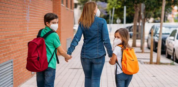 Mother walking with her children, boy and girl, go to school wearing masks during the coronavirus pandemic