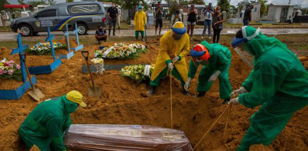 Gravediggers bury a COVID-19 victim while surrounded by relatives at the Nossa Senhora Aparecida cemetery in Manaus, Amazonas state, Brazil, on January 13, 2021, amid the novel coronavirus pandemic. - In Manaus there is a shortage of hospital beds as cases increased at an alarming rate. The city, with two million inhabitants, had already experienced nightmarish scenes in April and May, with mass graves and refrigerated trucks parked in front of hospitals to pile up the dead. But the situation is even worse in the beginning of 2021, since between January 1 and 11, at least 1,979 people were admitted to hospitals due to the virus, against 2,128 for the whole month of April, the worst since the start of the pandemic. (Photo by MICHAEL DANTAS / AFP)