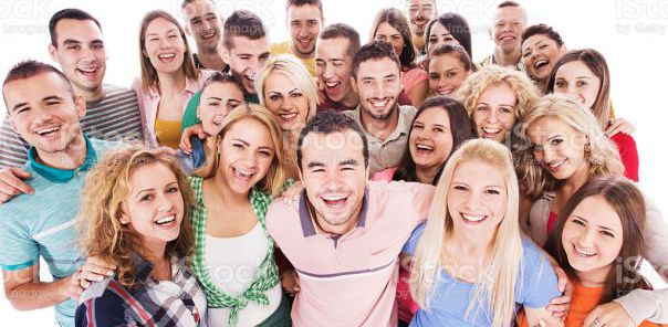 Large group of happy young people standing embraced and looking at the camera. Isolated on white.